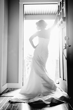 Bride in wedding dress leaning on the front door